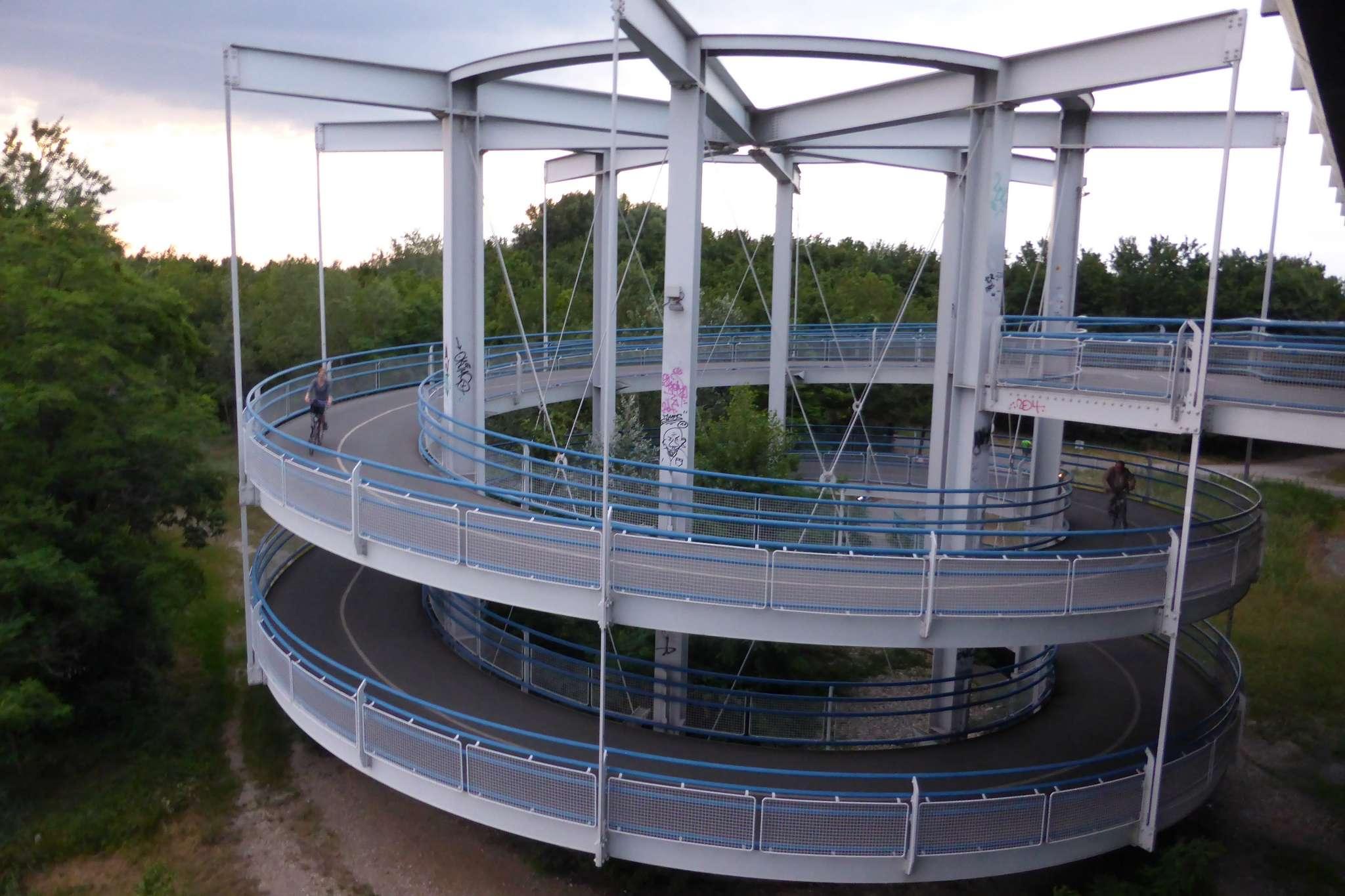 Ponieważ mosty wznoszą się wysoko nad lustrem wody, austriaccy projektanci zaplanowali ślimakowe podjazdy dla rowerzystów. Dzięki nim pochyłość staje się znacznie łagodniejsza i bardzo szybko można wspiąć się na wysokość kładki rowerowej.